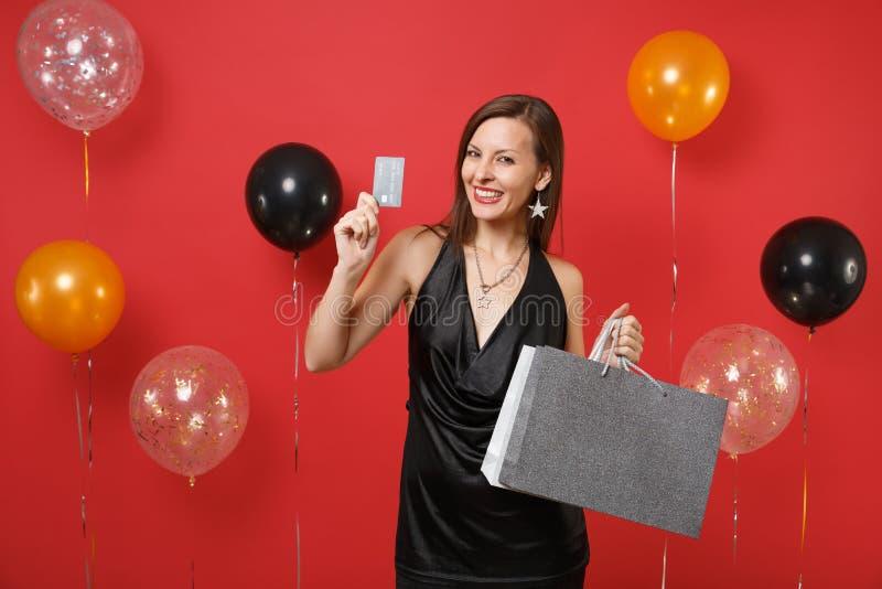 Mooi jong meisje in de zwarte creditcard van de kledingsgreep, gekleurde pakkettenzakken met aankopen na het winkelen op helder r royalty-vrije stock foto's