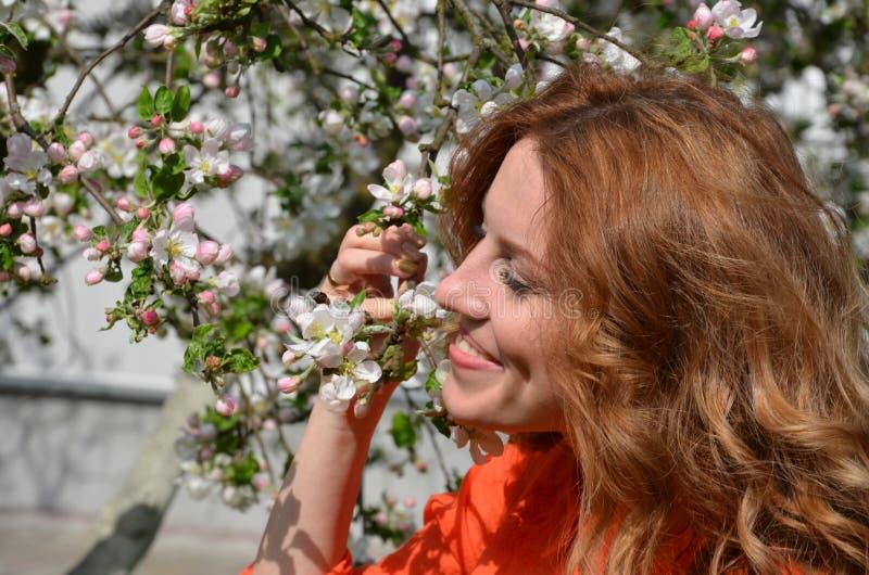 Mooi jong meisje die een geur van de lentebloemen ruiken stock foto
