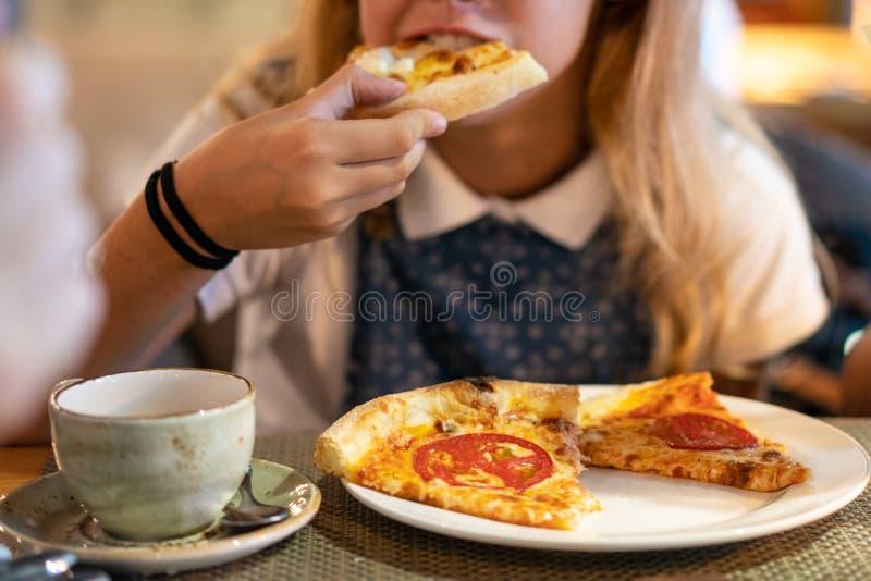 Mooi jong meisje die een plak van pizza eten stock foto