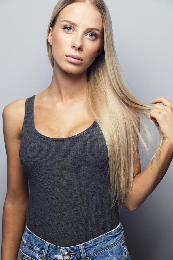 Mooi jong meisje die haar blondehaar houden stock fotografie