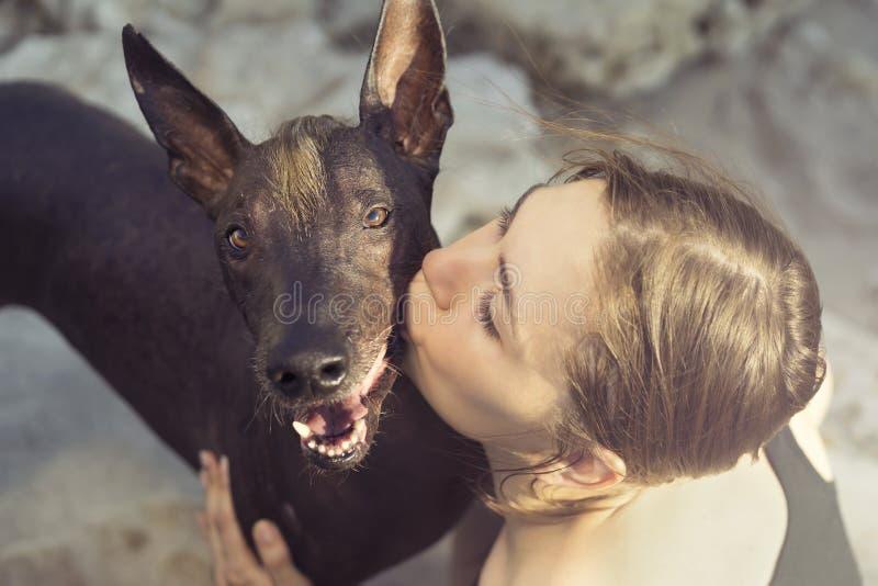 Mooi jong meisje die haar hondras kussen xoloitzcuintle, de zomer op een steenachtig strand bij zonsondergang royalty-vrije stock fotografie