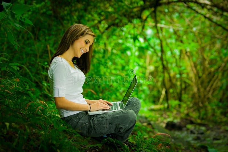 Mooi jong meisje die laptop in openlucht in met behulp van stock afbeeldingen