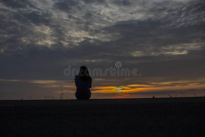 Mooi jong meisje die op de zonsondergang in het water letten stock foto's