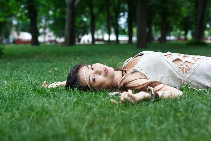 Mooi jong meisje die op gras in de zomerpark liggen stock afbeeldingen