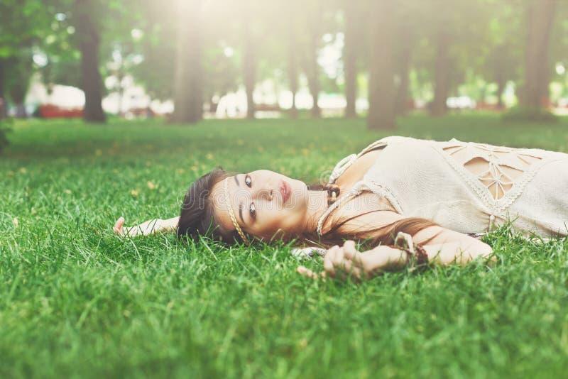 Mooi jong meisje die op gras in de zomerpark liggen royalty-vrije stock fotografie