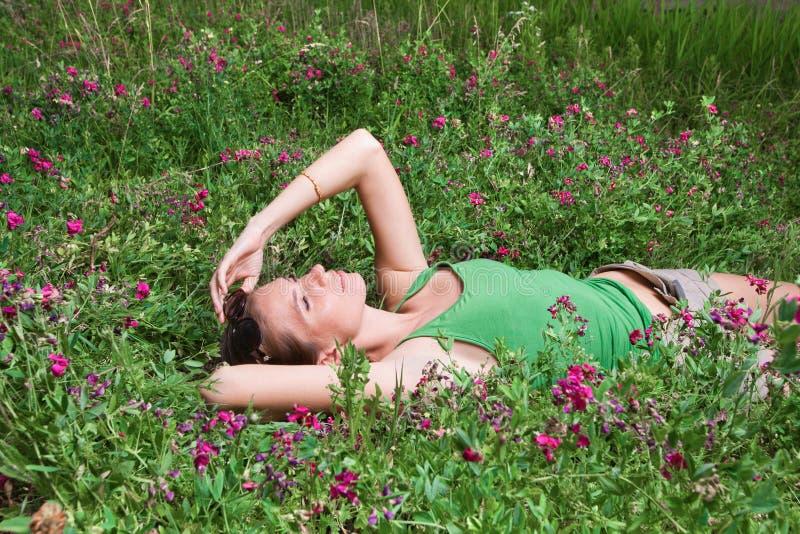 Mooi jong meisje die op groen gras liggen royalty-vrije stock foto