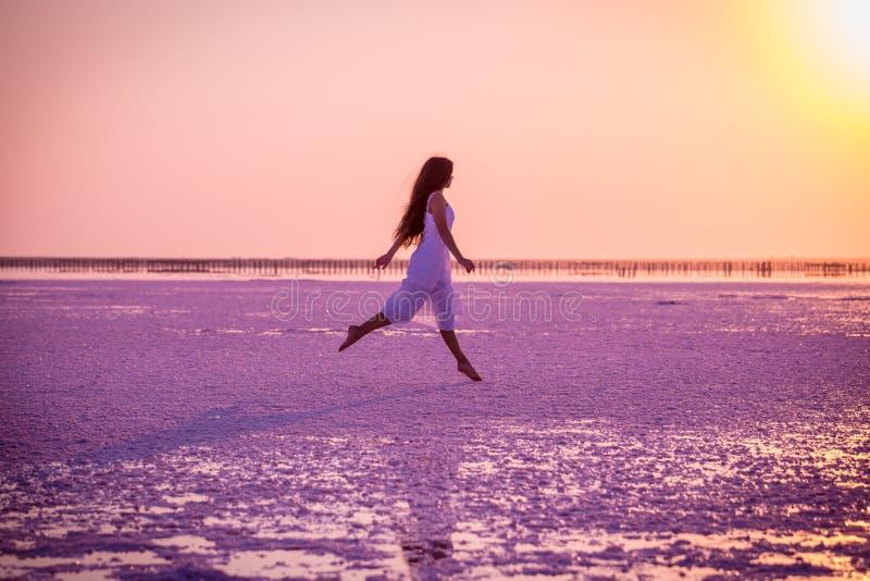 Mooi jong meisje die op het zoute meer bij zonsondergang springen stock afbeeldingen