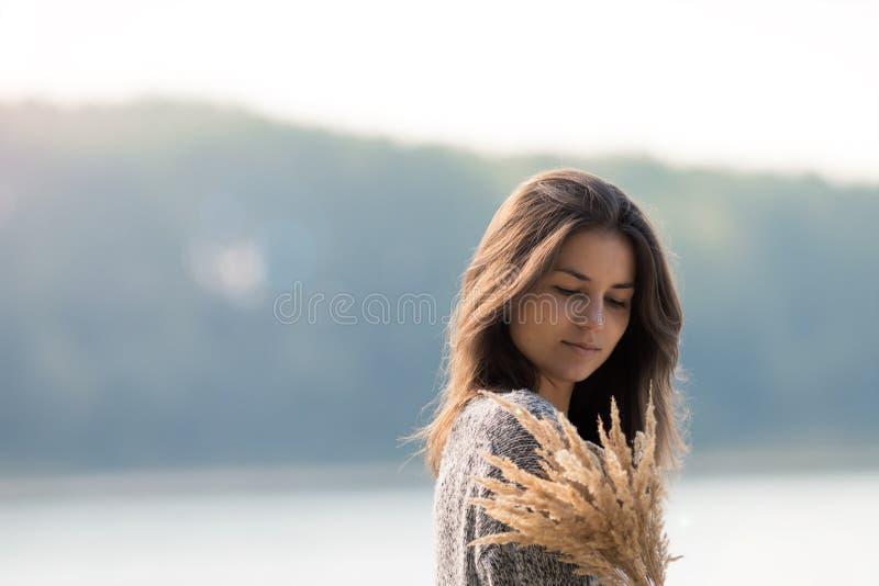 Mooi jong meisje die zich door het meer bevinden stock afbeeldingen