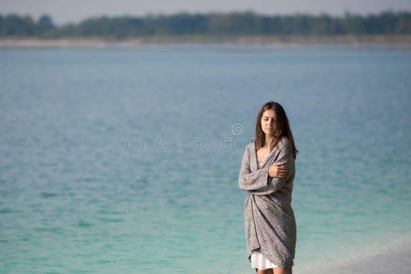 Mooi jong meisje die zich door het meer bevinden stock foto
