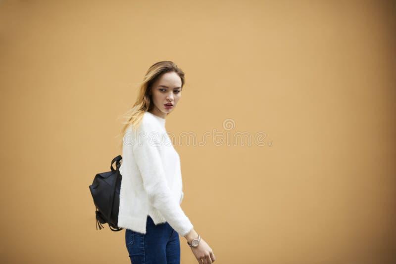 Mooi jong meisje in een lichte sweater op een gele muurachtergrond stock foto