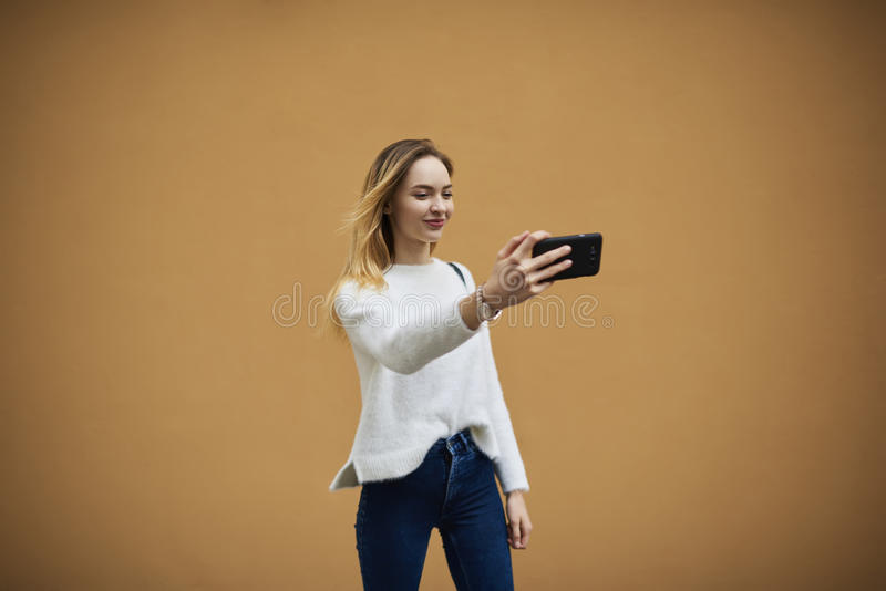 Mooi jong meisje in een lichte sweater op een gele muurachtergrond die vrije in openlucht 4G Internet-verbinding gebruiken stock afbeeldingen