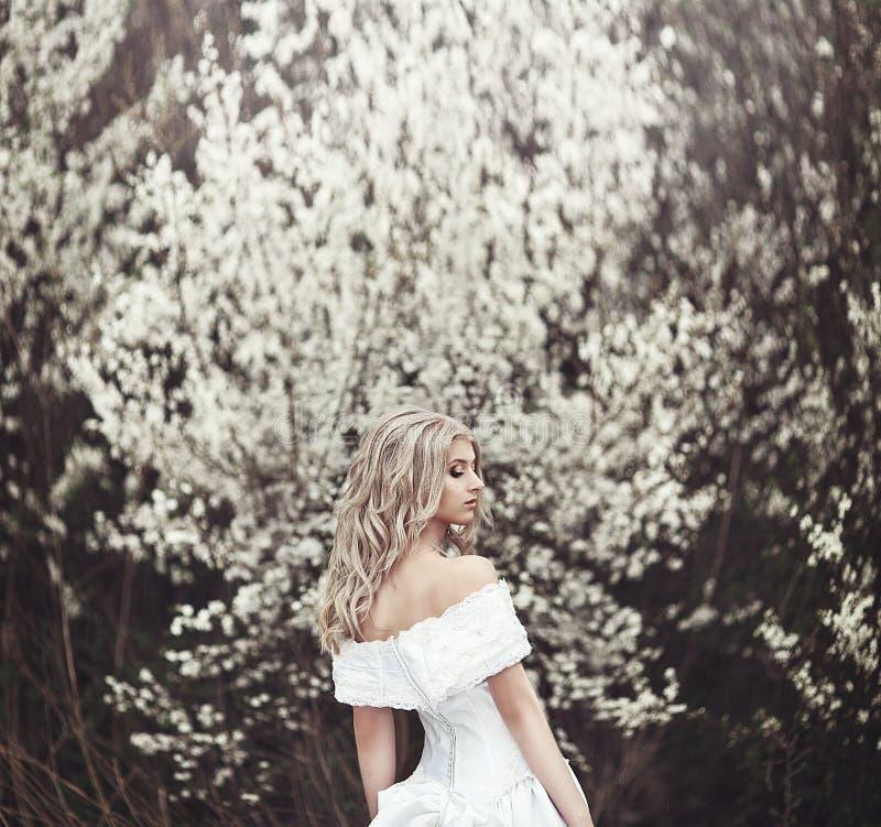 Mooi jong meisje in een mooie witte kleding dichtbij een bloeiende boom stock afbeelding