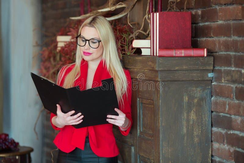 Mooi jong meisje in een rood jasje en het dragen van glazen stock afbeeldingen