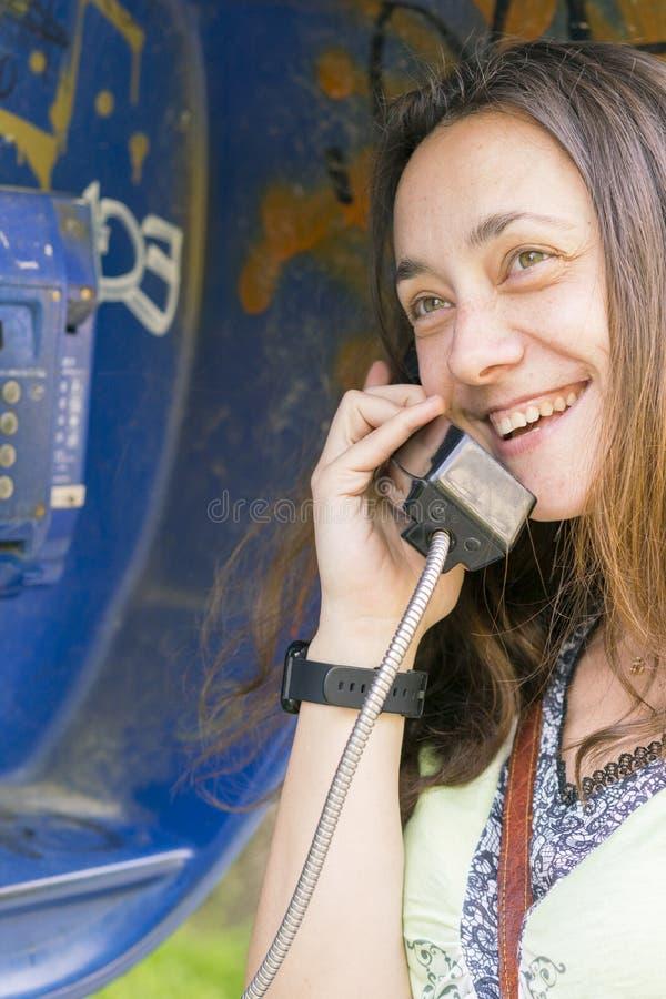 Mooi jong meisje in een telefooncel Het meisje spreekt op de telefoon van payphone mooi tienermeisje die door publiek spreken stock afbeelding