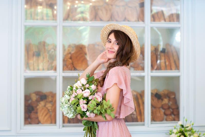 Mooi jong meisje in een zacht roze kleding, die een boeket van rozen in één hand houden Gelukkige vrouw die een strohoed op backg royalty-vrije stock fotografie