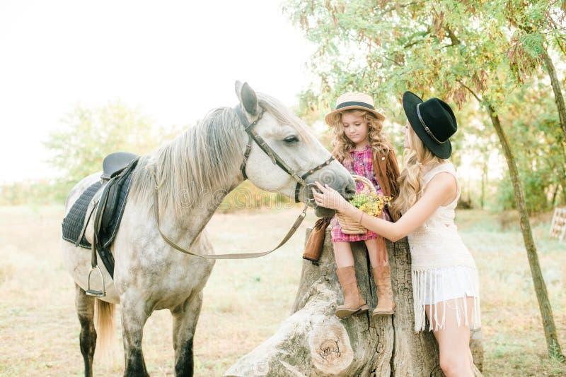 Mooi jong meisje met blond haar in een suèdejasje met rand met weinig zuster in een strohoed en een geruite uitstekende kleding royalty-vrije stock foto's