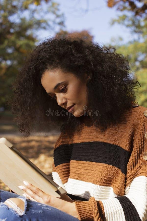 Mooi jong meisje met donker krullend haar die tabletcomputer met behulp van, openlucht stock foto
