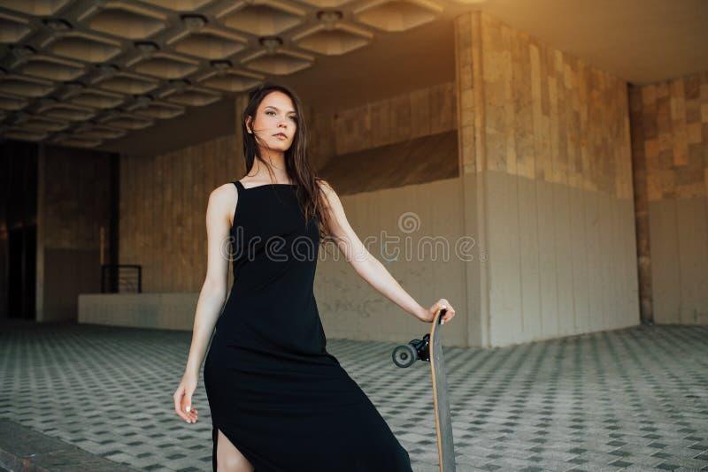 Mooi jong meisje met een lange raad in de stad Het concept de moderne jeugd Actieve pretvakantie stock foto's