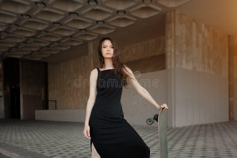 Mooi jong meisje met een lange raad in de stad Het concept de moderne jeugd Actieve pretvakantie stock fotografie