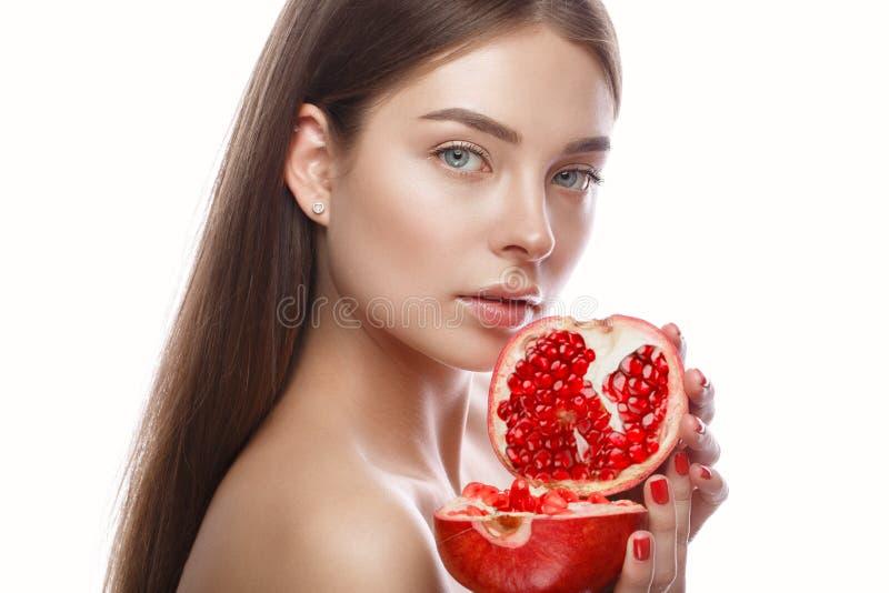 Mooi jong meisje met een lichte natuurlijke samenstelling en perfecte huid met granaatappel in haar hand Het Gezicht van de schoo royalty-vrije stock fotografie
