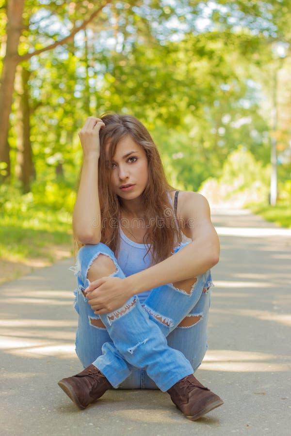Mooi jong meisje met lang haar die jeans dragen en een witte t-shirtzitting op de weg in de dag van de hout heldere Zonnige zomer stock afbeeldingen