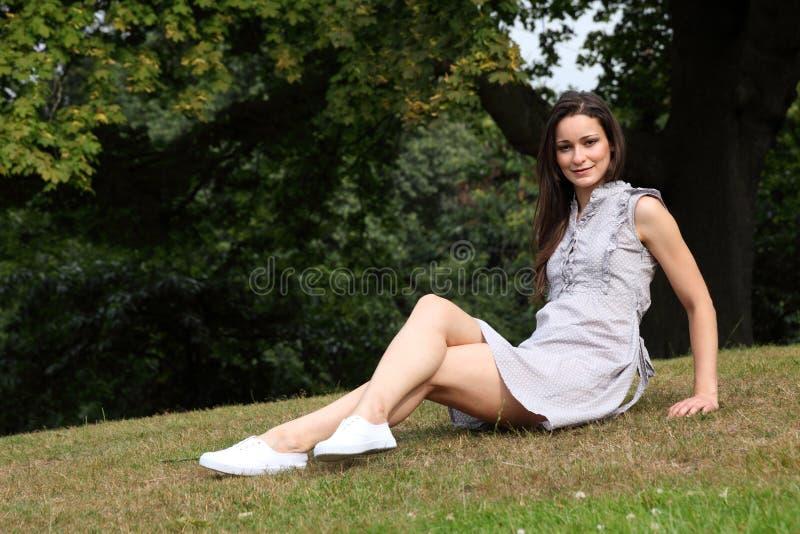 Mooi jong meisje met lange benen op gras in park stock foto's