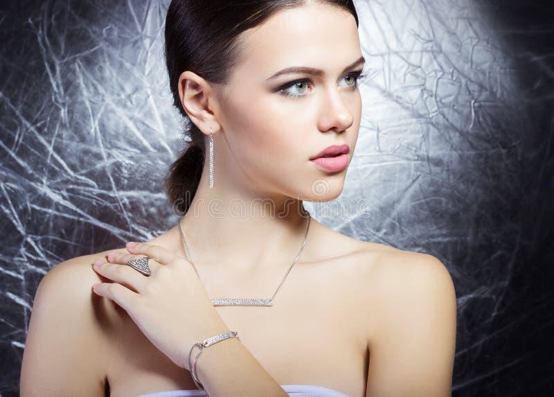 Mooi jong meisje met mooie modieuze dure juwelen, halsband die, oorringen, armband, ring, in de Studio filmen stock afbeeldingen