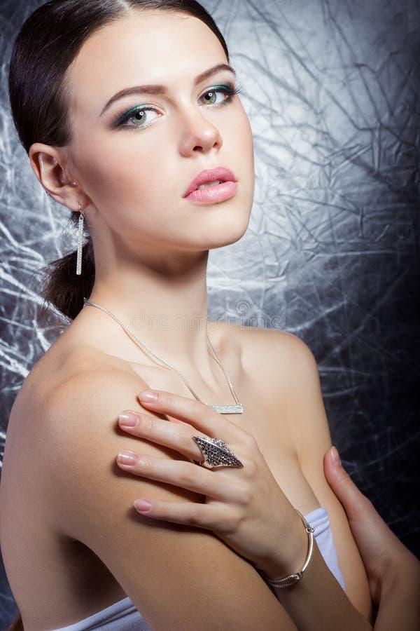 Mooi jong meisje met mooie modieuze dure juwelen, halsband die, oorringen, armband, ring, in de Studio filmen royalty-vrije stock foto's