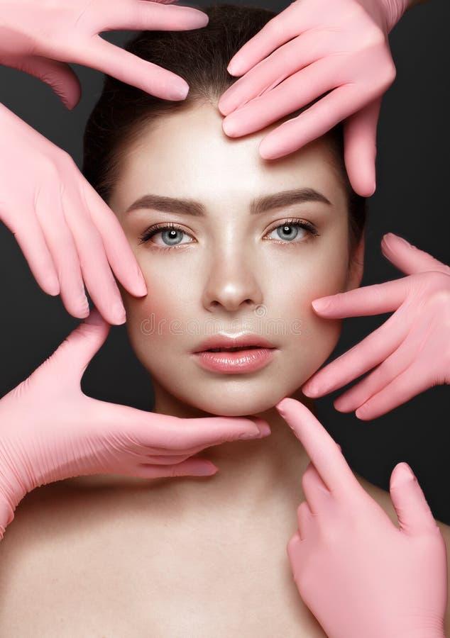 Mooi jong meisje met natuurlijke naakte samenstelling met kosmetische hulpmiddelen in handen Het Gezicht van de schoonheid stock afbeelding