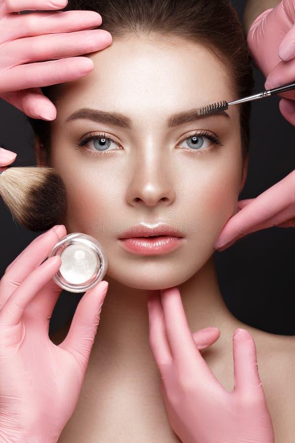Mooi jong meisje met natuurlijke naakte samenstelling met kosmetische hulpmiddelen in handen Het Gezicht van de schoonheid royalty-vrije stock fotografie