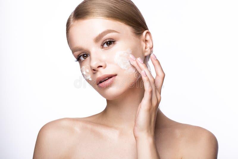 Mooi jong meisje met room op de huid, Franse manicure Het Gezicht van de schoonheid stock fotografie