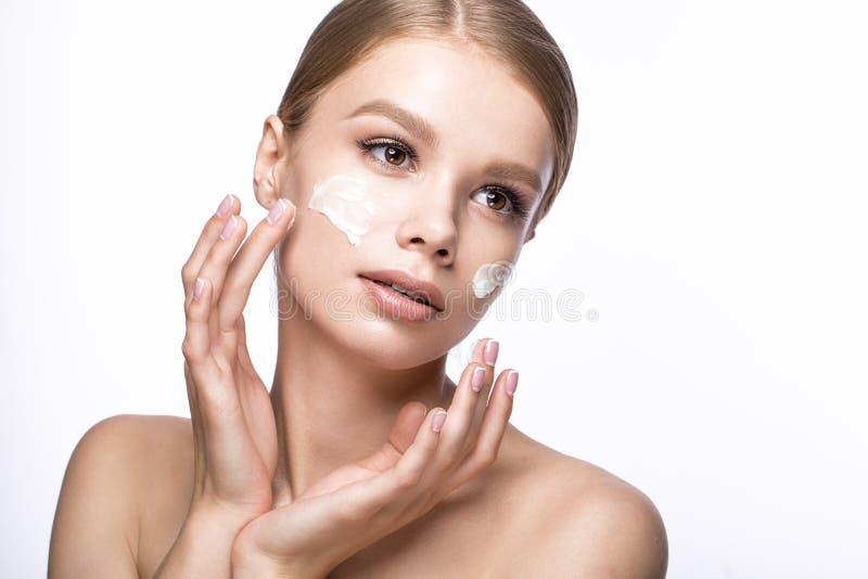 Mooi jong meisje met room op de huid, Franse manicure Het Gezicht van de schoonheid stock afbeelding