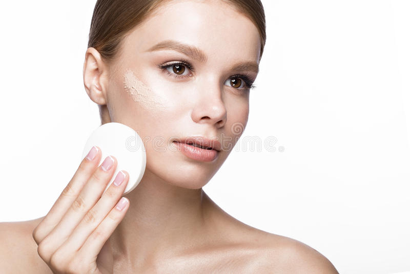 Mooi jong meisje met spons voor toepassingssamenstelling en Franse manicure Het Gezicht van de schoonheid stock afbeeldingen