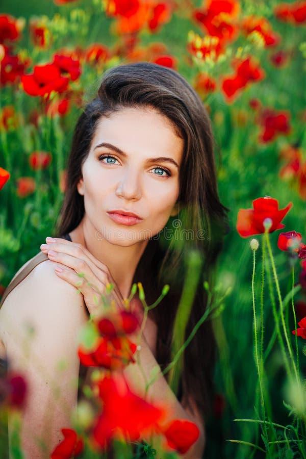 Mooi jong meisje op papavergebieden bij zonsondergang royalty-vrije stock afbeelding