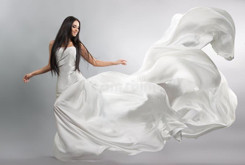 Mooi jong meisje in vliegende witte kleding Stromende Stof Het lichte witte doek vliegen stock foto
