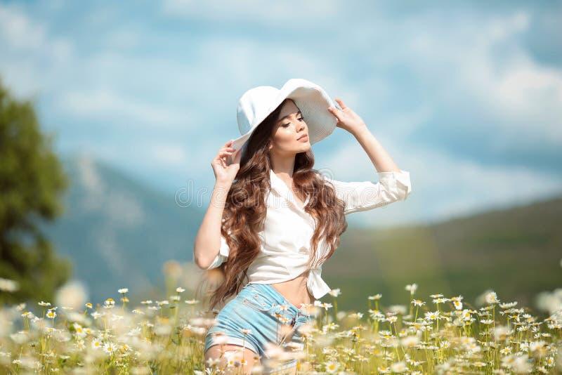 Mooi jong meisje in witte hoed over kamillegebied Onbezorgde gelukkige donkerbruine vrouw met gezond golvend haar die pret hebben stock afbeeldingen