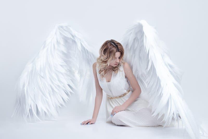 Mooi jong model met grote engelenvleugels die in de studio zitten stock fotografie