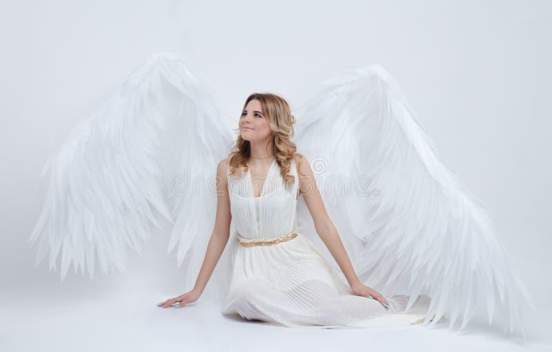 Mooi jong model met grote engelenvleugels die in de studio zitten stock afbeeldingen
