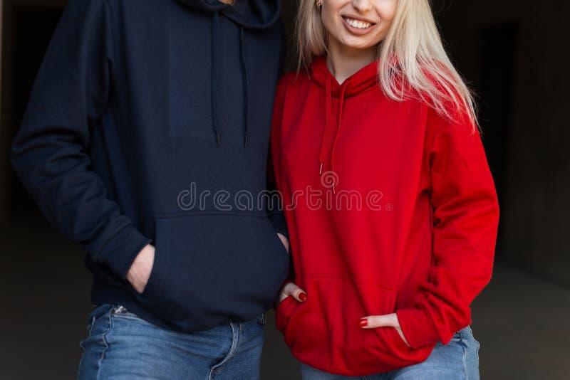 Mooi jong modieus paar in in hoodie binnen met zonneschijn Hipster gelukkig meisje in rode hoodie en knappe mens stock foto