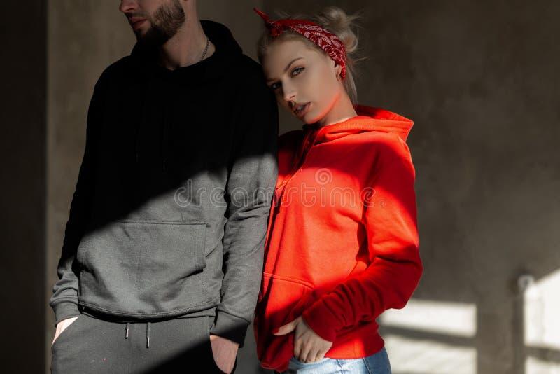 Mooi jong modieus paar in in hoodie binnen met zonneschijn Hipstermeisje in rode hoodie en knappe mens met baard stock afbeelding