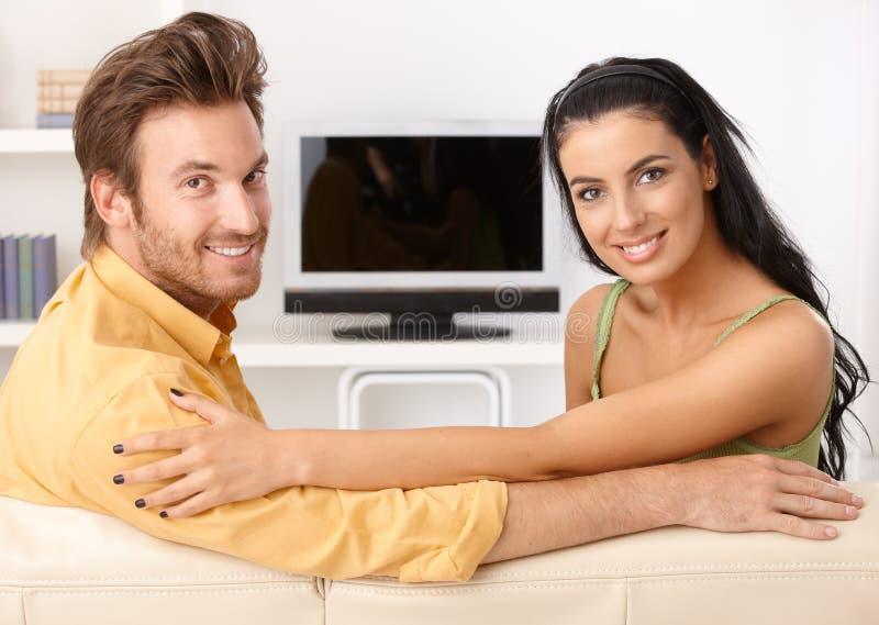 Mooi jong paar dat op bank glimlacht royalty-vrije stock fotografie