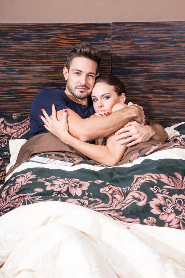 Mooi jong paar die in bed worden doen schrikken stock foto's