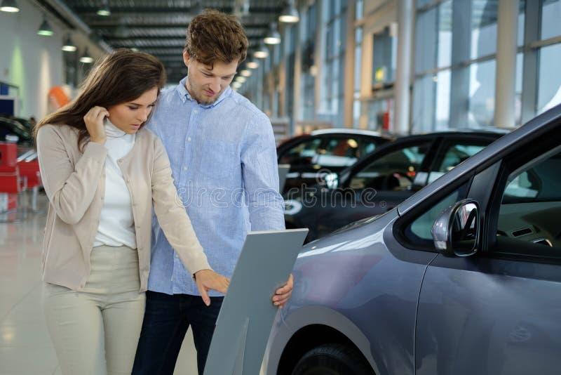 Mooi jong paar die een nieuwe auto de het handel drijventoonzaal bekijken stock afbeelding