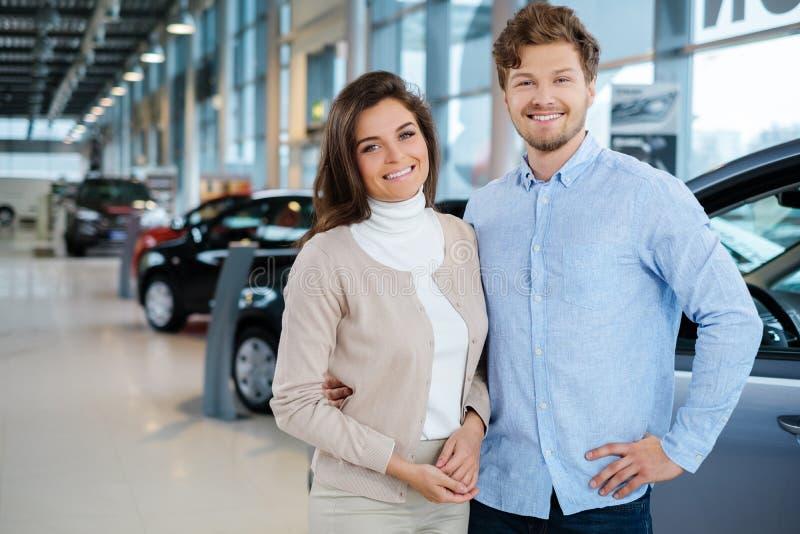 Mooi jong paar die een nieuwe auto de het handel drijventoonzaal bekijken stock foto