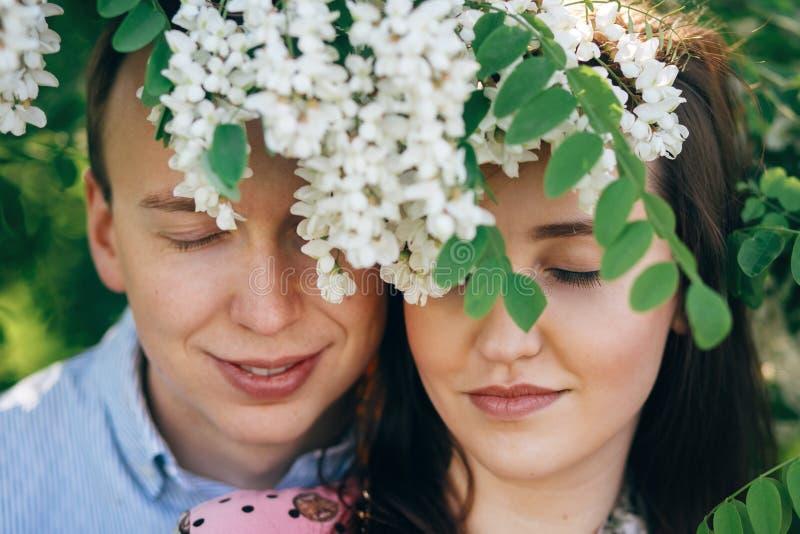 Mooi jong paar die en onder witte bloemen in de lentetuin stellen glimlachen Portretten die van gelukkige familie bij het bloeien stock foto