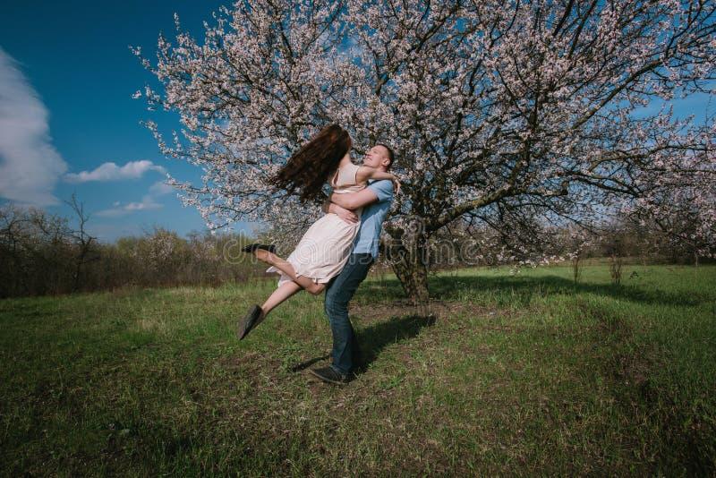 Mooi jong paar die en pret op blauwe hemelachtergrond dansen hebben stock foto