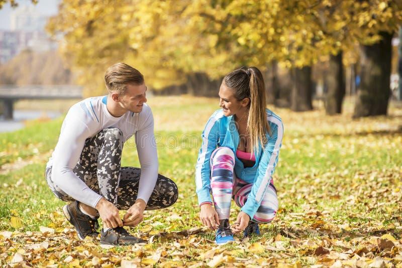 Mooi jong paar die hun schoenen voor looppas in het park voorbereiden stock afbeelding