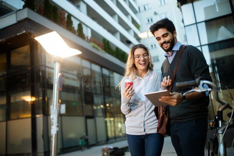 Mooi jong paar die onderaan de straat met tablet lopen stock foto