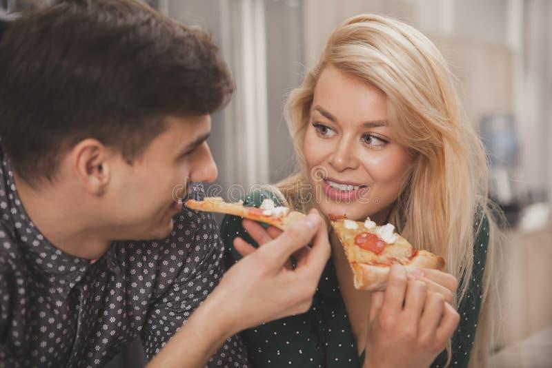 Mooi jong paar die pizza eten samen bij de keuken stock foto