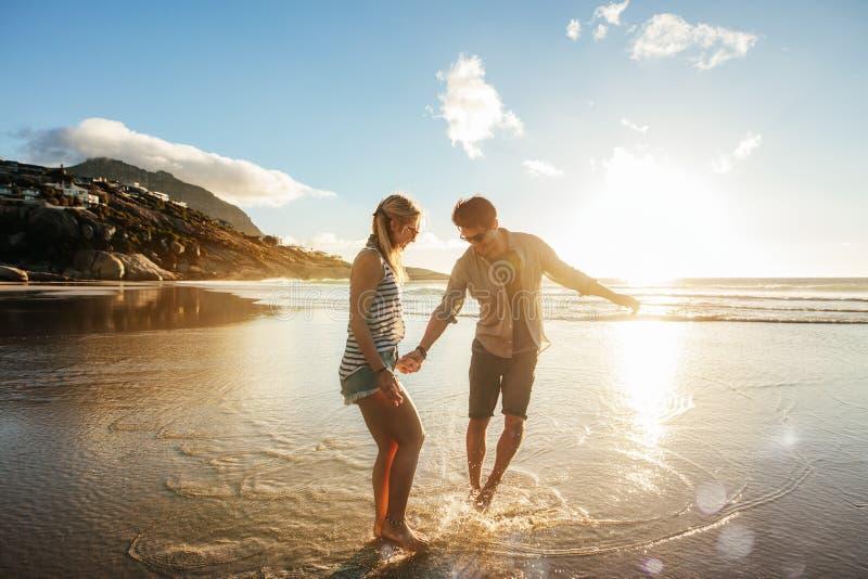 Mooi jong paar die pret op strand hebben stock foto's